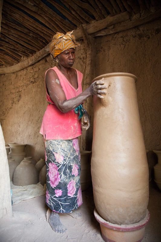 A woman skillfully throws the clay between her hands as she works to mold a tall, thin pot half her size.