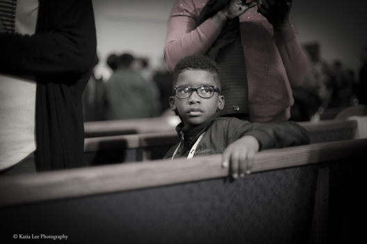 Young boy watches the cameras and reporters after a Hillary Clinton shared the stage with mother's of gun violence at Central Baptist Church in Columbia S.C. February 24, 2016