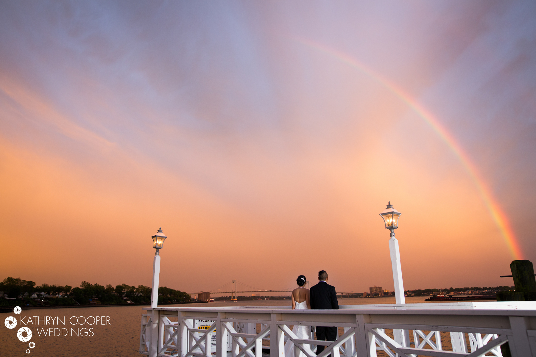 NYC elopement photographer in Bronx captures couple standing under rainbow after NYC storm