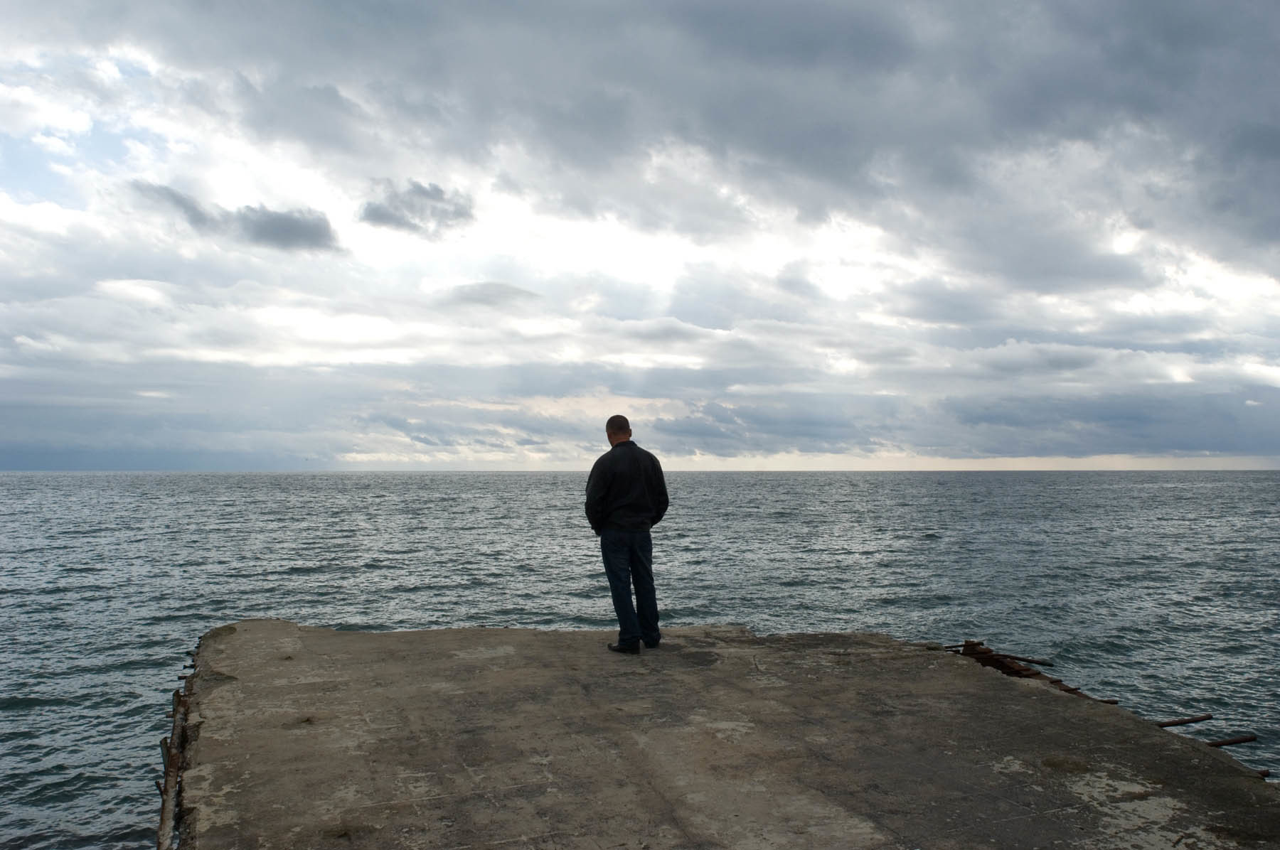 A lone man looks outward over the Black Sea on a broken pier.