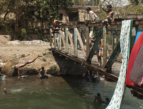 Boys jump off a bridge into the polluted river.