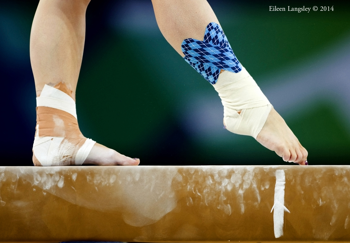 A generic image of a gymnast sporting tartan ankle taping while competing on beam during the Gymnastics competitions at the 2014 Glasgow Commonwealth Games.