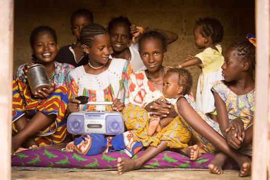 Ouagadougou, Burkina Faso: July 6, 2007.  A group of young Fulani women and children in eagerly crowd into the house for a photo. One of them dashes back outside, only to reappear moments later with a radio, which she proudly displays on her lap for all the world to see.