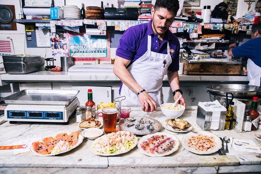 Marino Peradotto places (L-R) smoked salmon toast, combination seafood salad, half dozen oysters, Sicilian sashimi, crab back, and a Dozen Eggs on the counter at Swan Oyster Depot in San Francisco, Calif. on Tuesday, April 2, 2019.