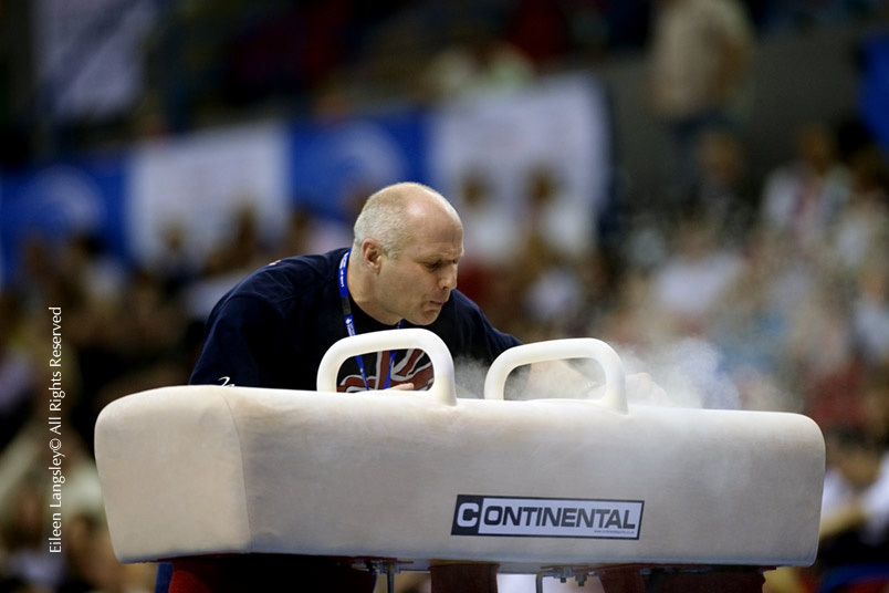 A portrait image of British National Coach Andrei Popov preparing the pommel horse before his gymnast competes.