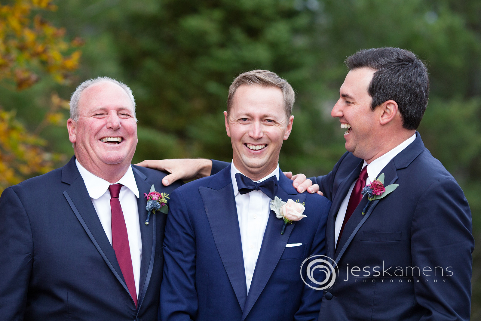 groomsman and best man laugh with their friend
