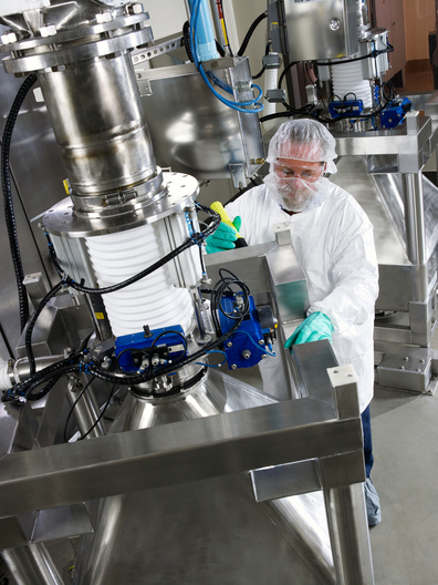 Research chemical operator Daniel Steinberg checking for proper docking between a product storage container and the outlet of a large scale pin mill. The milling process is used to decrease the particle size of active pharmaceutical ingredients.