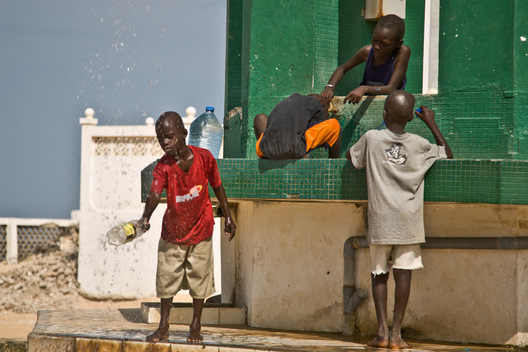 "Children wash at the well of Diamalaye (zem-zem holy water) in front of the Seydina Limamou Laye Mausoleum, which sits on the coast of Senegal in the fishing village of Yoff.  Seydina Limamou Laye (1843-1909) was the founder of the Layne (meaning ""partisans of God"") brotherhood."