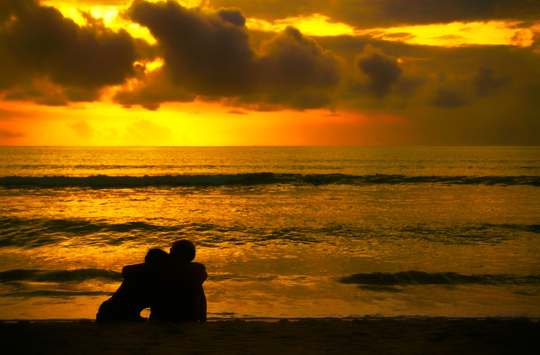 Romantic couple sitting and hugging on the beach at sunset silhouette, Bali, Kuta Beach, Indonesia