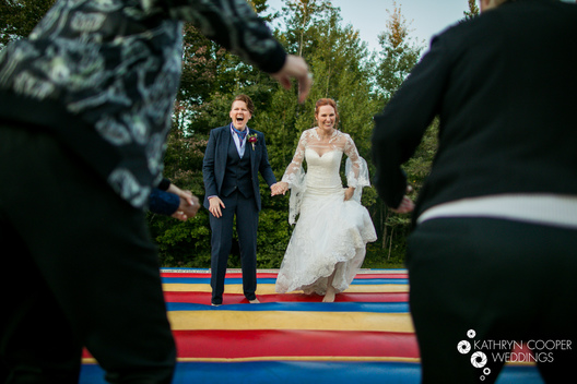 lgbtq wedding photographer maine, bar harbor - jump fun bouncy house bride and bride