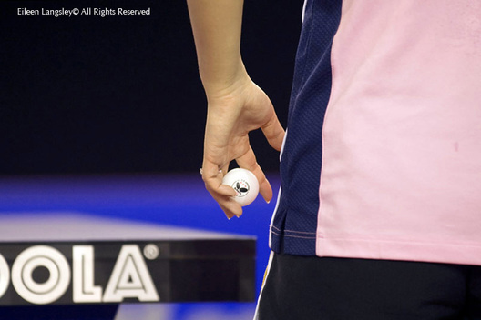 A generic cropped image of the hand of a table tennis player holding the ball and about to serve.