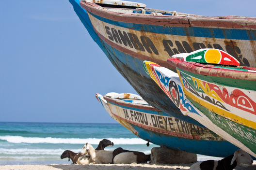 As I eat, black and white-spotted sheep and goats snooze in the shade of colorfully-painted boats that lined the beach.