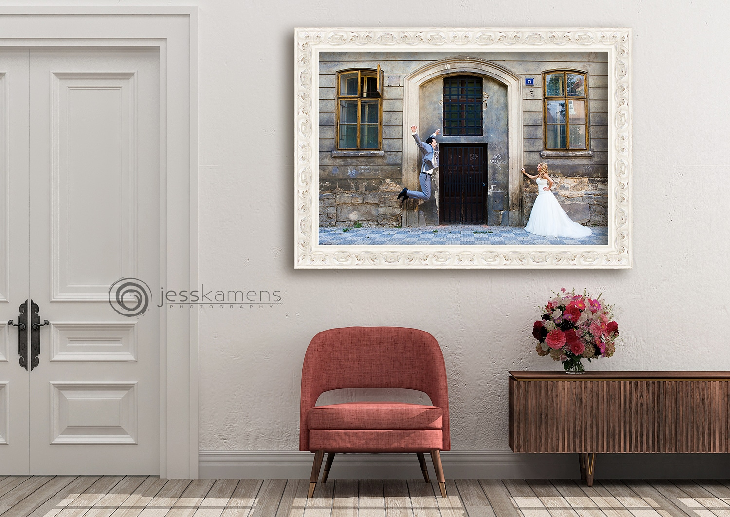 a wedding portrait hangs on the wall of a home above a red chair and a sideboard