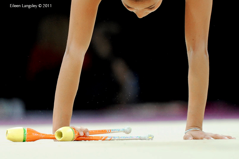 A cropped generic image of a gymnast competing with Clubs at the World Rhythmic Gymnastics Championships in Montpellier.