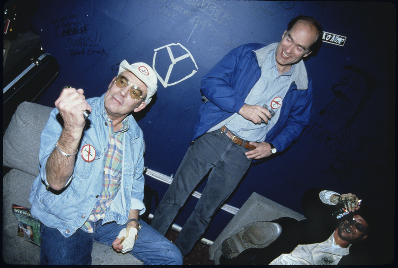 Hunter S. Thompson, Aspen Mayor John Bennett, and local columnist Dan Dunn at a voter registration party in Aspen, CO on 11/7/95. Thompson is spraying a permanent dye ink throughout the room, and Dunn has taken face full. Thompson was later arrested that night for driving while alcohol impaired.  Michael Brands. 970-379-1885.