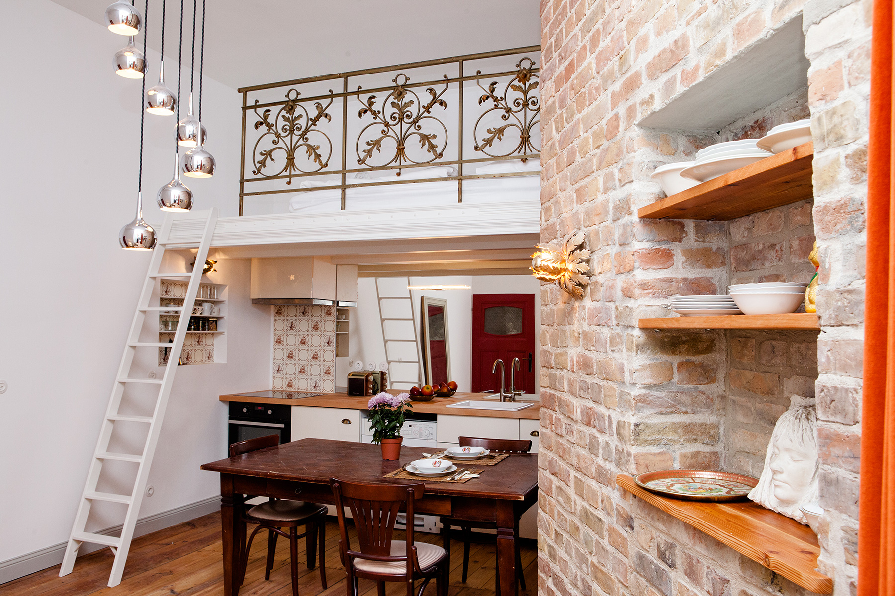 property photography image of a loft room with a brick wall and a kitchen with a ladder