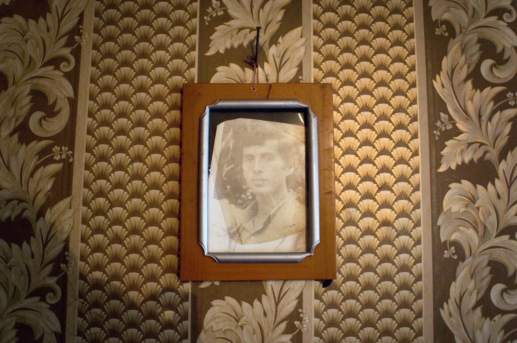 A lone photo of lost kin hangs in a lone farmhouse north of the Ochamchire district.