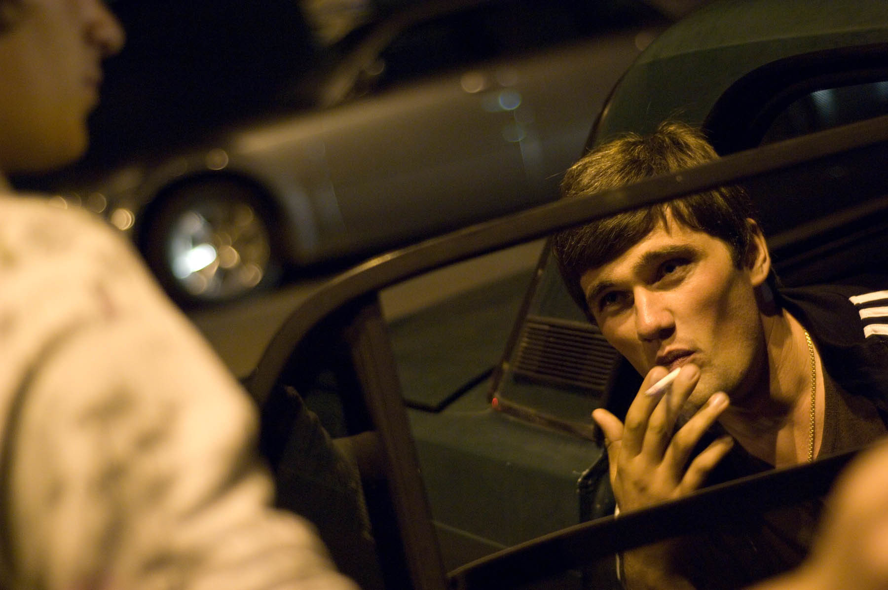 Young men spend many evenings smoking and conversing around their vehicles on the promenade in Sukhum.