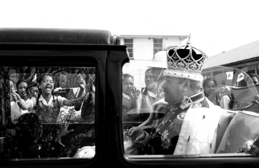 "Coronation Day: Following the Coronation of His Majesty King George Tupou V, the King drives through the streets of Nuku'alofa in the Kingdom of Tonga.  The streets were lined with school children shouting ""Long Live the King""."