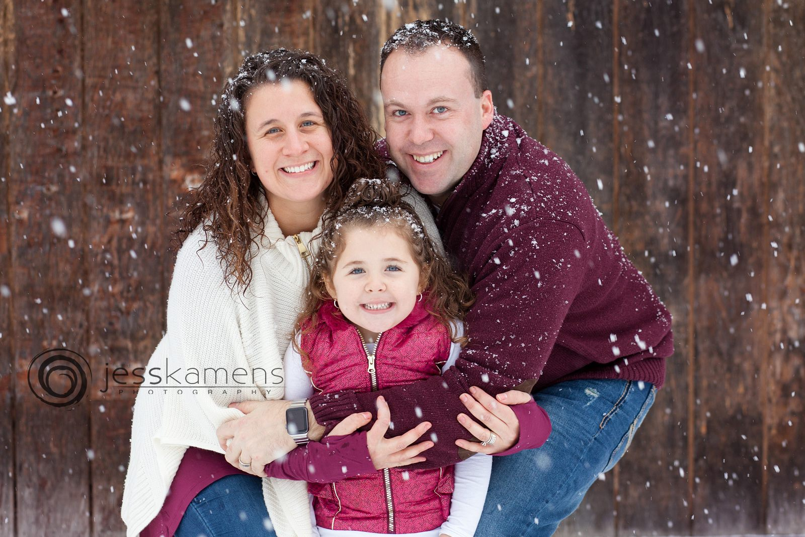 family against a wooden background during their snow session