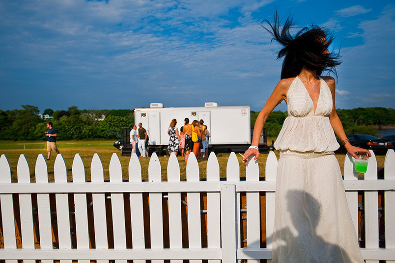 A woman stands against a fence at The Mercedes-Benz Polo Challenge at Two Trees Farm in Bridgehampton, NY.