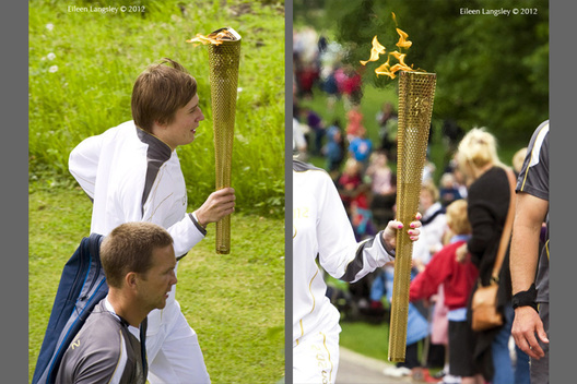 Flanked by security local youth Ben Hope carries the Olympic Torch and Flame in the gardens of Chatsworth House in Derbyshire during the Torch Relay.
