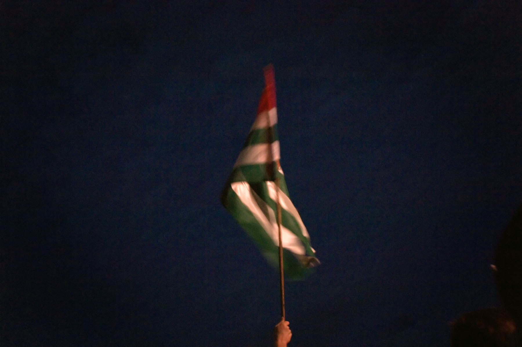The national flag is waved by a solo carrier in the middle of the evening.