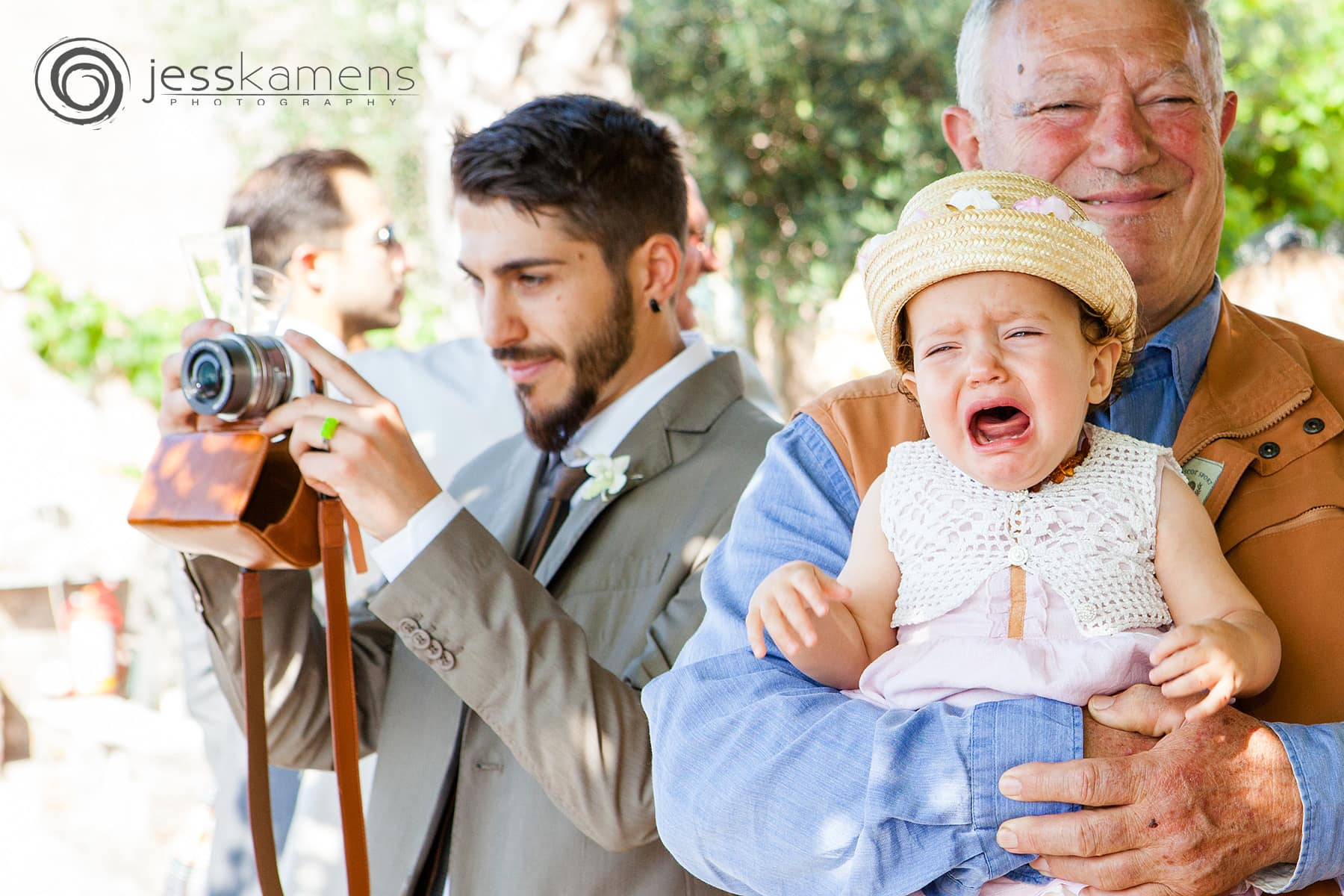 baby crying in his grandfather's arms and another person taking a picture in the background taken by a wedding photographer rochester