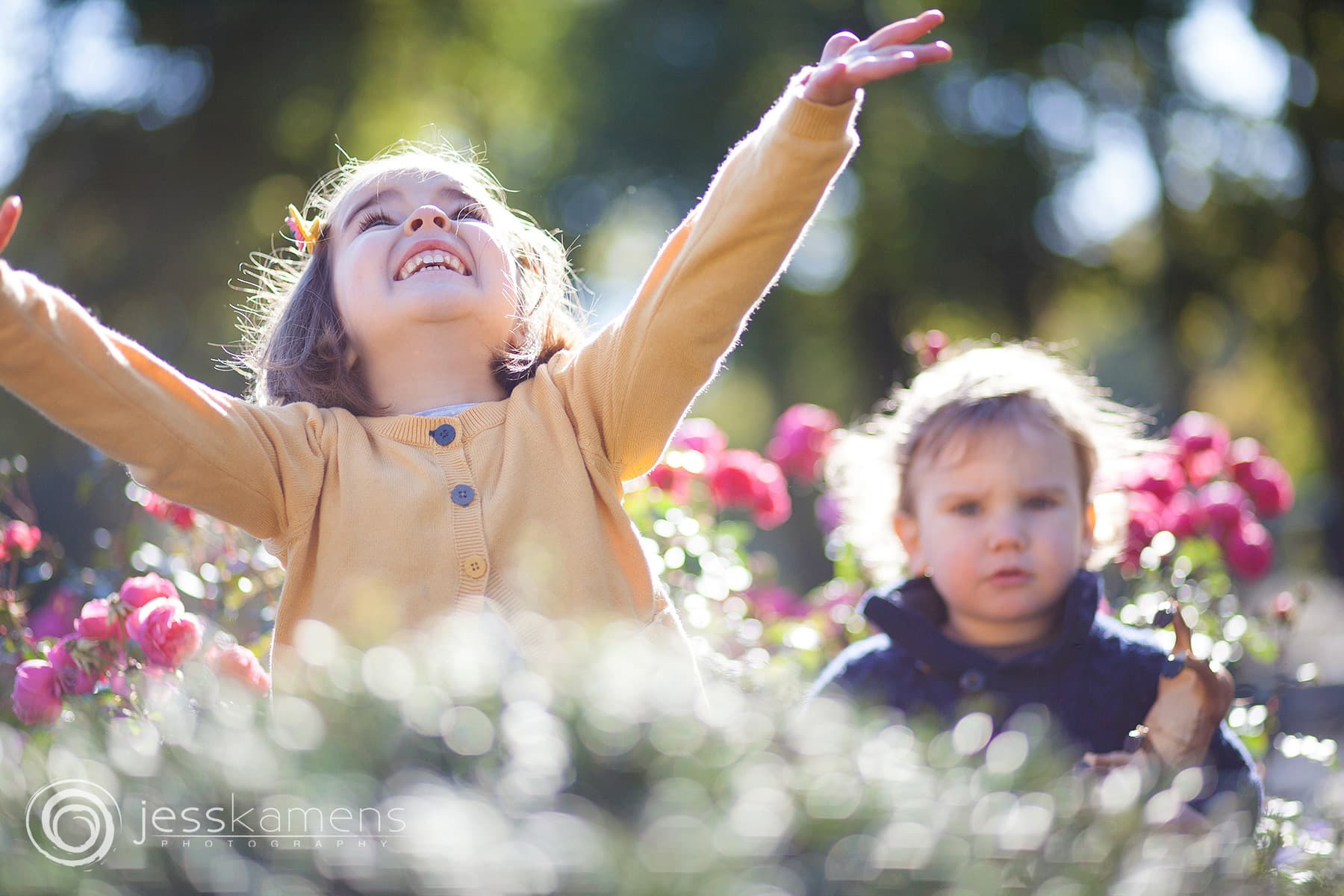 a little girl throws flowers in the air while her brother looks on confused in the background