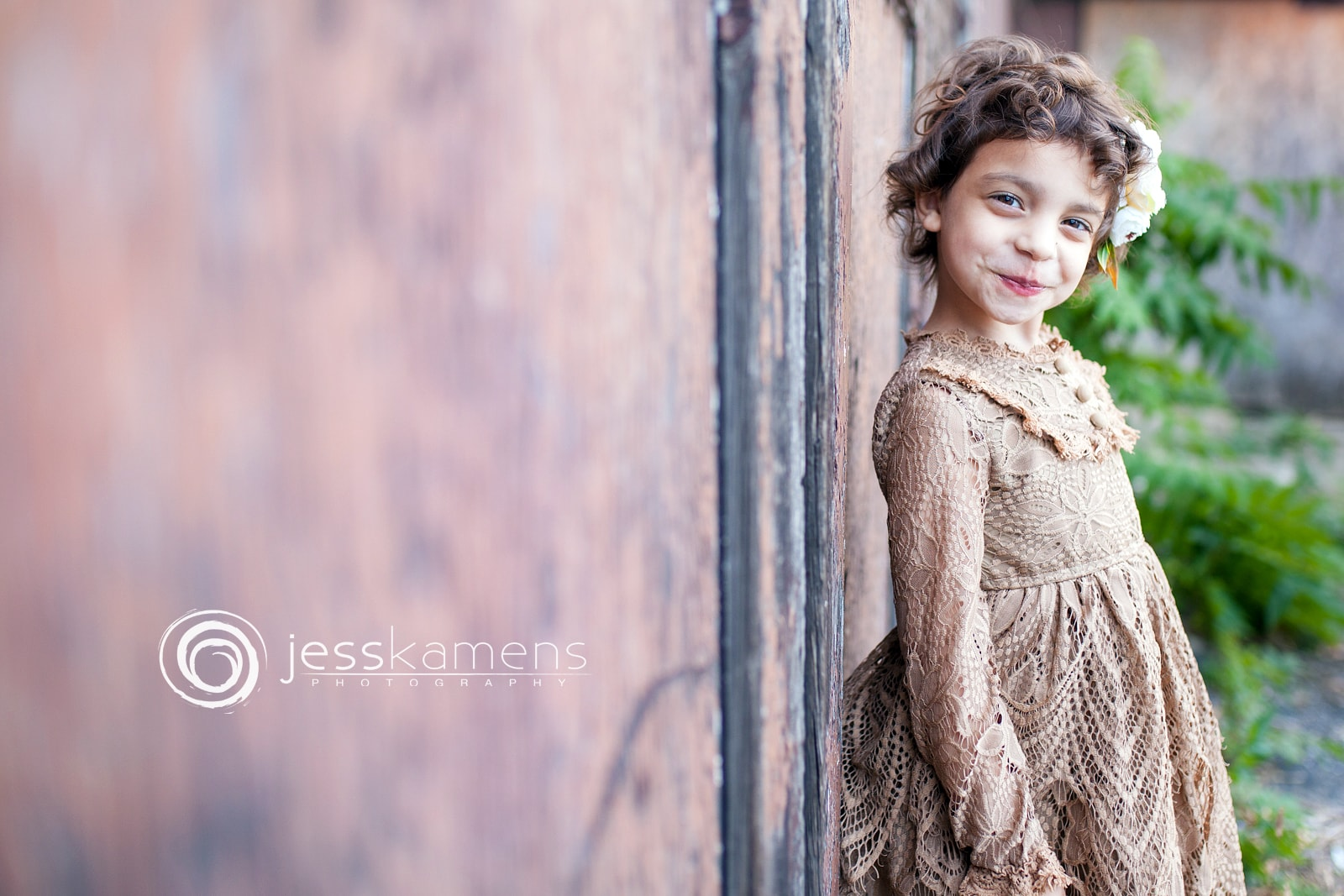 A stunning, sweet girl leaning against a rusty wall with a beautiful, lace, brown dress on. She has a flower in her hair.