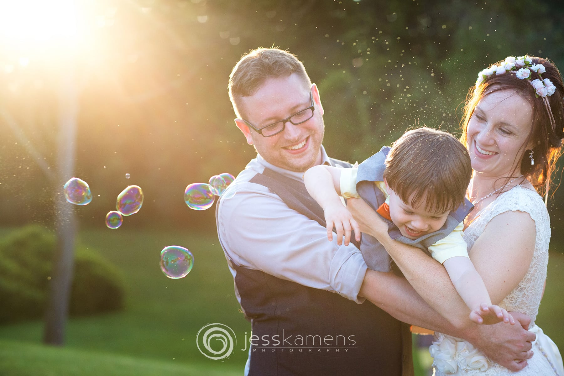 a bride and groom hold their son against the backlit evening light while playing with bubbles taken by rochester ny photographers