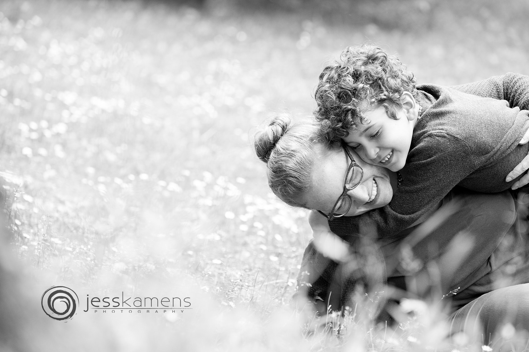 mother and child in black and white wrestling in the field during their family photoshoot
