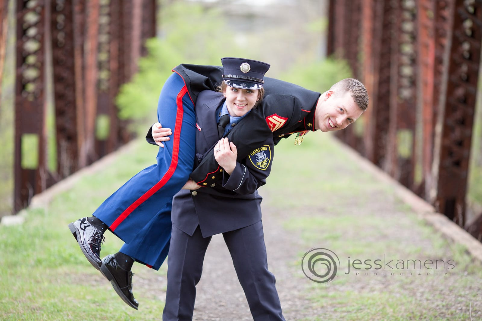 wedding photographers in rochester ny love to use unique bridges and such to capture images like this firefighter holding her marine fiance on her back for their engagement photos