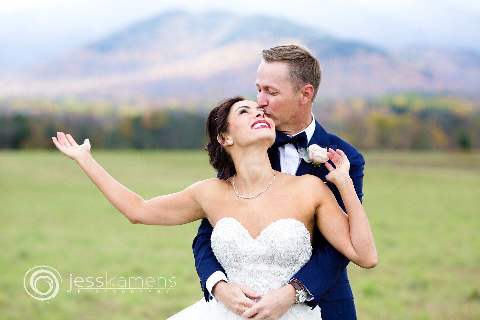 This beautiful destination wedding was in lake placid new york and you can see the mountains in the background. The groom is hugging the bride and this was taken by a destination photographer in new york