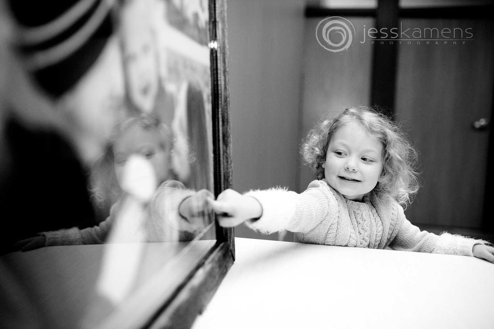 a little girl admires her family portrait and touches the glass with her finger while smiling.