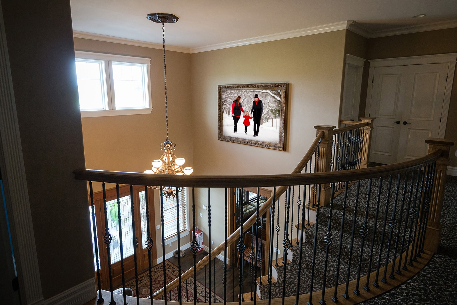 a family portrait hangs in a stairway of the home for all to admire. The family is walking in the snow with snow-covered trees.
