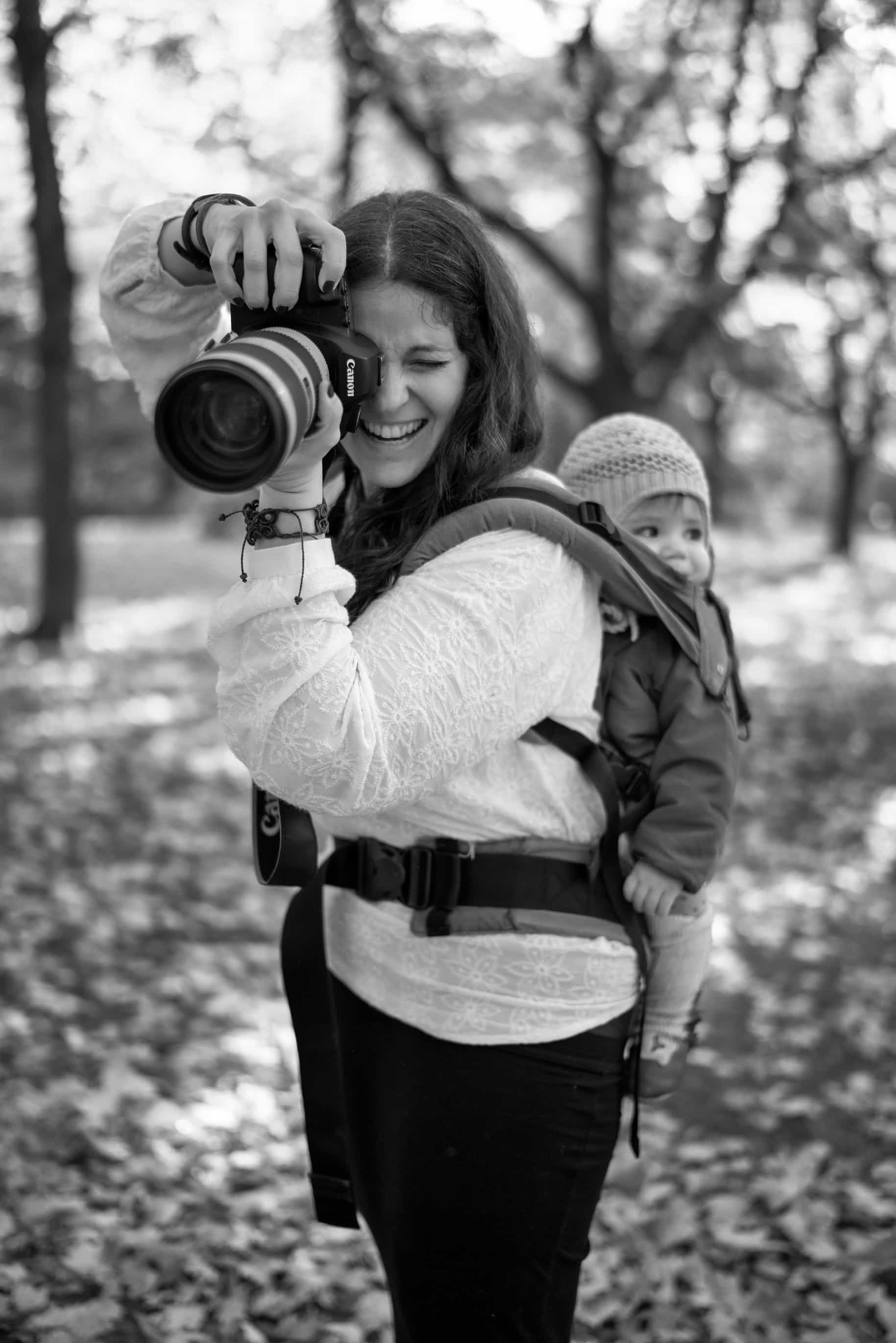 an image of a photographer with a child on her back in a carrier babywearing