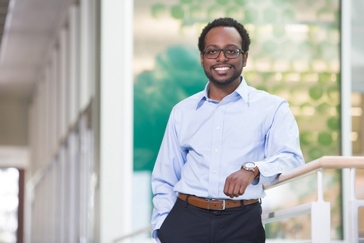 Editorial portrait of African American male wearing glasses and smiling by commercial photographer Nancy Rothstein