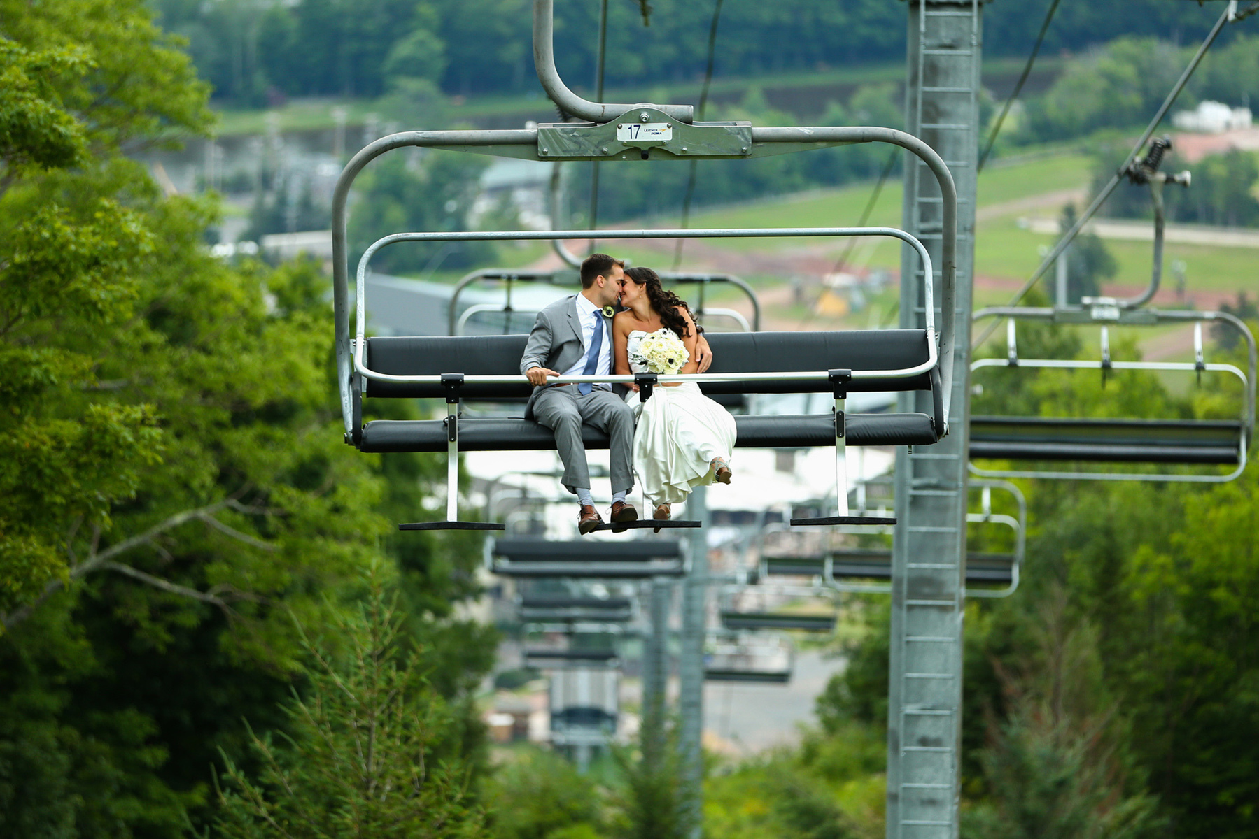 Hunter Mountain wedding on ski lift with happy couple by upstate NY wedding photographer. Unique mountain wedding on skilift