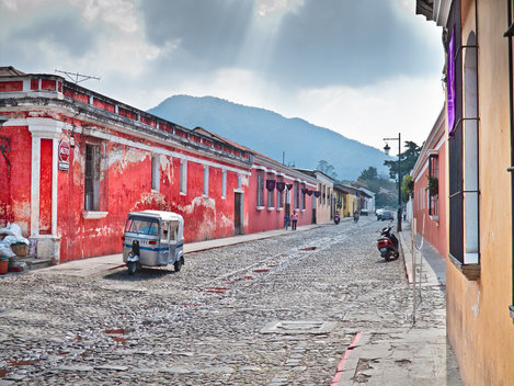Tuk tuk in a street of Antigua, Guatemala with a red building