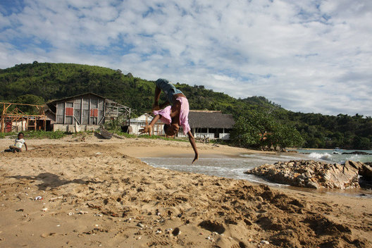 A young boy does flips on a beach in Nosy Komba.