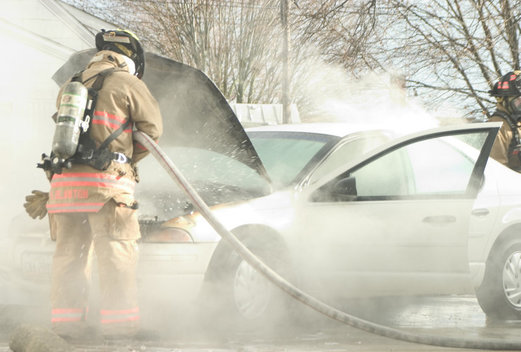 A firefighter douses flames coming from the engine of a car on Feb. 11 in Greenville. A tube burst and caused the engine fire. The driver was unharmed.