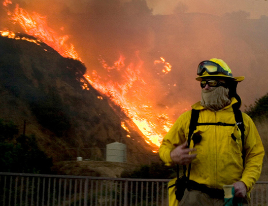A firefighter from Huntington Beach looks for his backup as the Brea fire rages behind him on Nov. 15. Several nearby fire departments were called in to help fight the blaze, which was difficult to do because of the hills and strong winds.