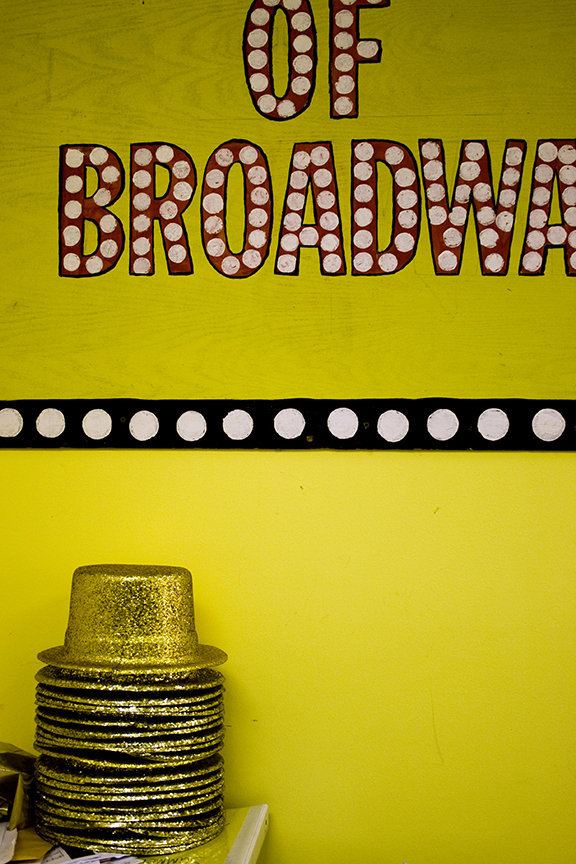 A stack of glittery, gold top hats sit in the MTA studio by a 100 years of Broadway mural.