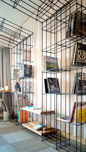 Steel frame bookshelves of AND cafe 3D printing cafe Interior Design by Singapore-based AND lab in Beijing.