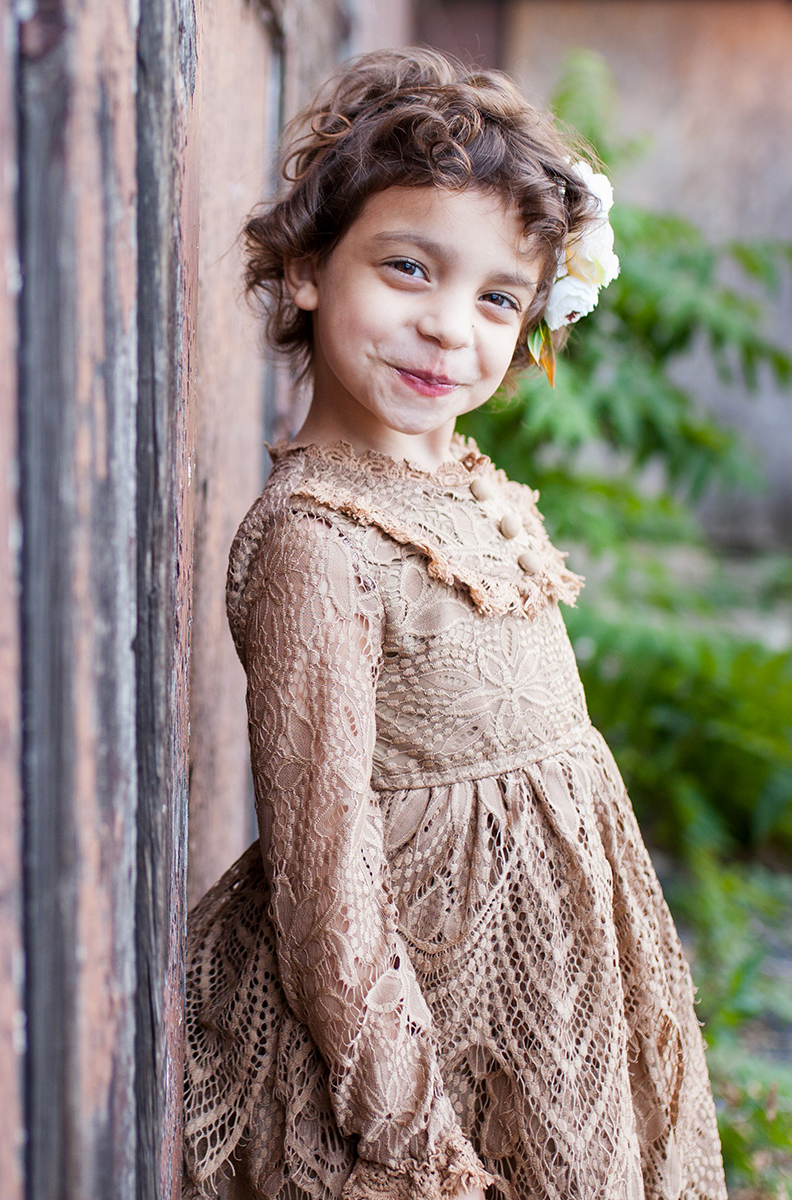 girl leaning against a rusty wall in a brown lace dress by a Rochester family photographer