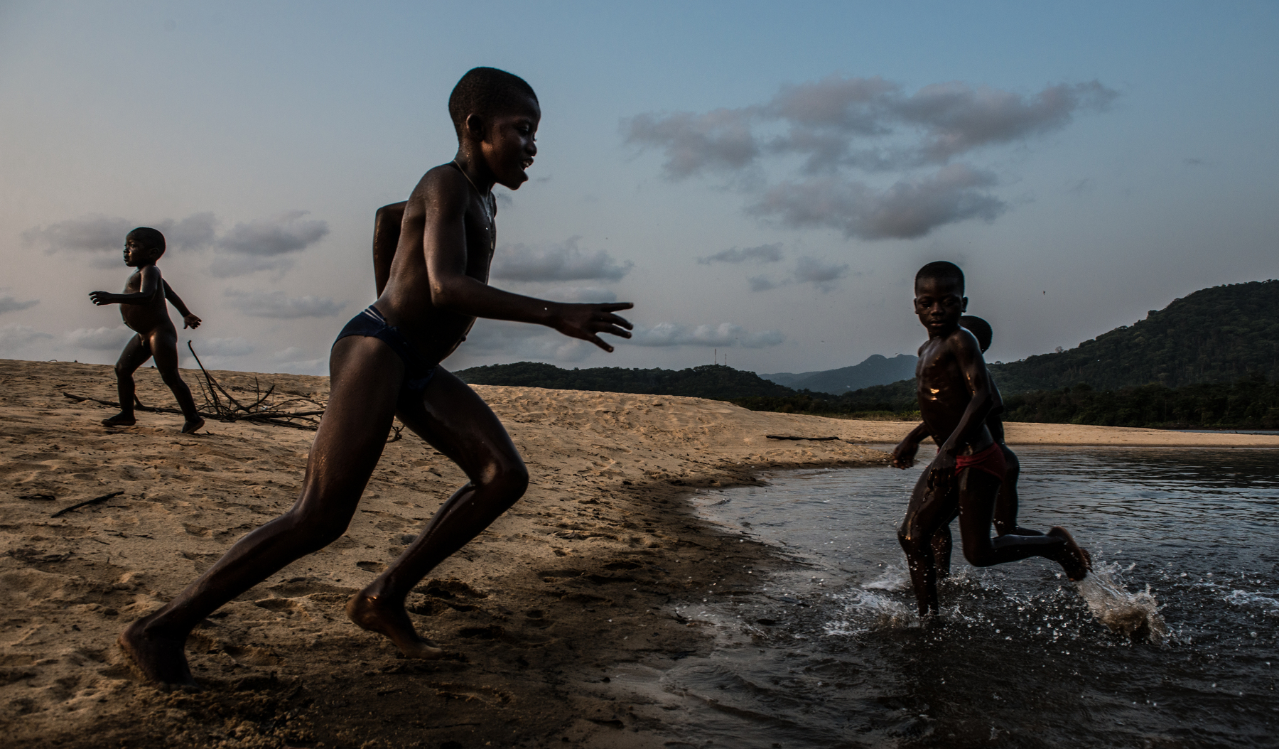 Young village children play in the lagoon at John Obey just before sunset.