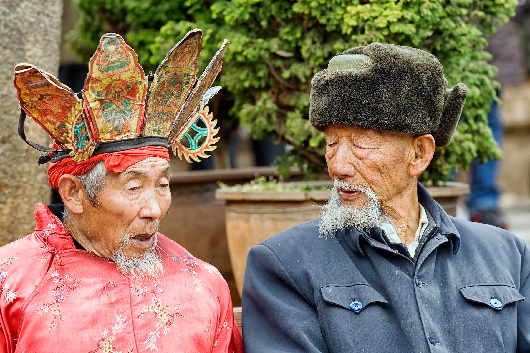 China, Naxi Dongba Shaman priest and old distinguished gentleman sitting on a bench talking, Lijiang, Old City, Sifang Square, Yunnan Province