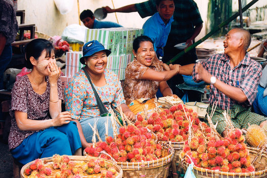 Myanmar, Burma, Rangoon, Yangon, People having fun selling rambutan fruit in a traditional market