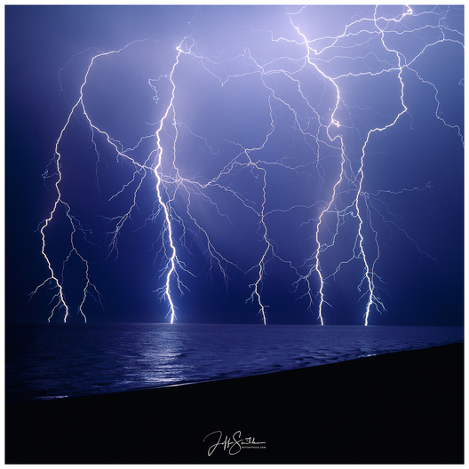 I set my camera up in anticipation of a storm I saw in Puerto Peñasco, Sonora.  It was exciting to see the lightning dance exactly across my camera's frame.  The flashing lightning froze the small waves in time.  1998   